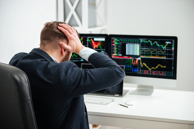 Achteraanzicht van een geschokte, gestresste zakenman die het hoofd bij de hand houdt op de werkplek op kantoor