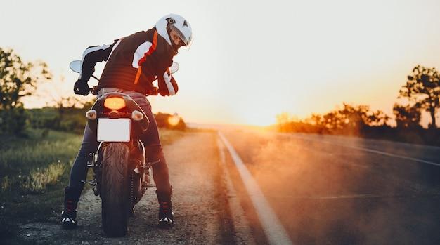 Achteraanzicht van een geweldige jonge fietser die terugkijkt voordat hij gaat reizen op zijn fiets tegen zonsondergang.