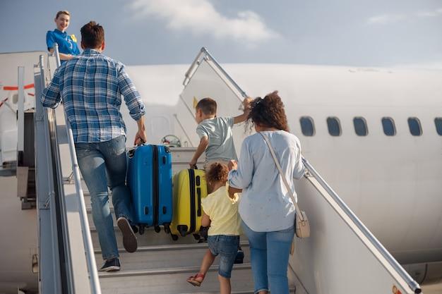 Achteraanzicht van een gezin van vier dat instapt, overdag aan boord gaat van het vliegtuig, klaar voor zomervakanties. mensen, reizen, vakantieconcept
