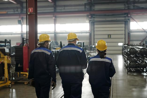 Achteraanzicht van een groep arbeiders of ingenieurs van een grote hedendaagse fabriek die langs de werkplaats met industriële apparatuur beweegt en praat