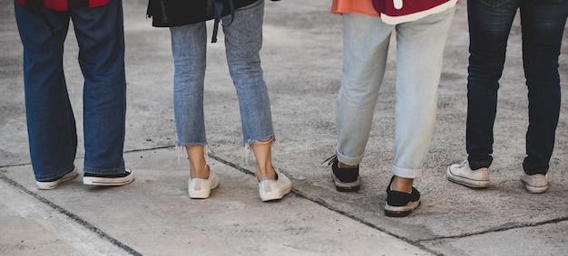 Achteraanzicht van een groep van vier jonge meisjes, studentenbenen en sneakers die samen op de universiteitscampus buiten staan. concept voor onderwijs, vriendschap en studentenleven.