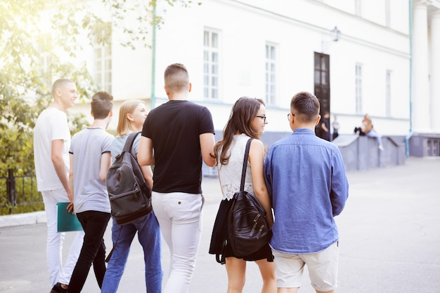 Achteraanzicht van een groep vrienden die op de studentencampus naar de universiteit lopen, leermiddelen vasthouden en vrolijk chatten