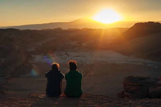 Achteraanzicht van een groep vrienden, die samen op een berg staan en naar de dageraad op de zonsopgang kijken