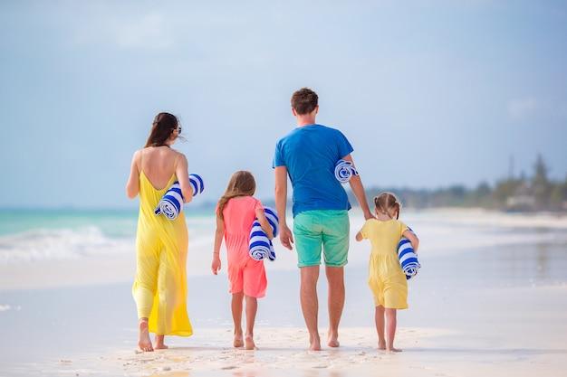 Achteraanzicht van een jong gezin op tropisch strand