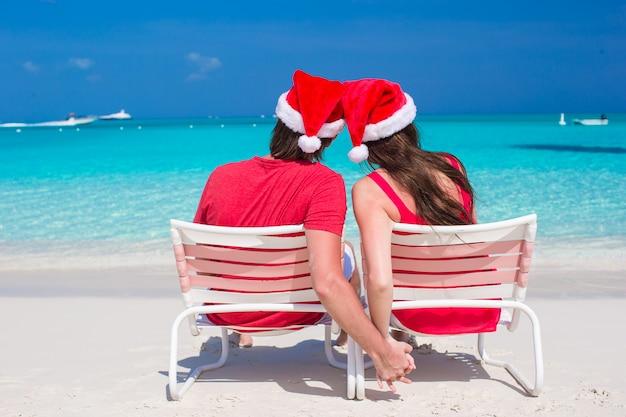 Achteraanzicht van een jong koppel in rode santa hats zittend op strandstoelen