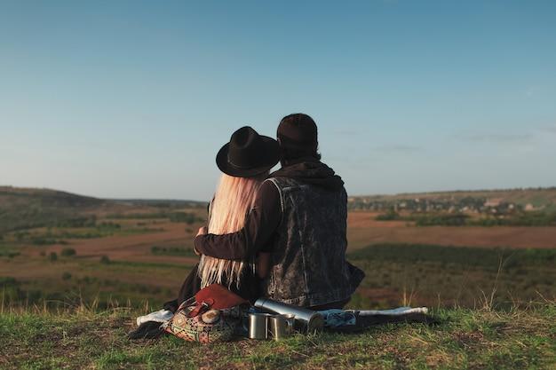 Achteraanzicht van een jong koppel knuffelen op picknick, achtergrond van blauwe hemel.