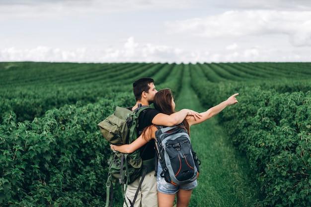 Achteraanzicht van een jong koppel met rugzakken op bes plantages. vrouw met lang haar wijst haar hand naar de horizon