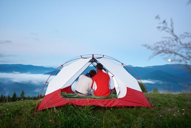 Achteraanzicht van een jong koppel zitten in een tent kijken naar de bergen in de ochtendnevel bij zonsopgang onder een blauwe hemel waarop de maan in de verte schijnt.