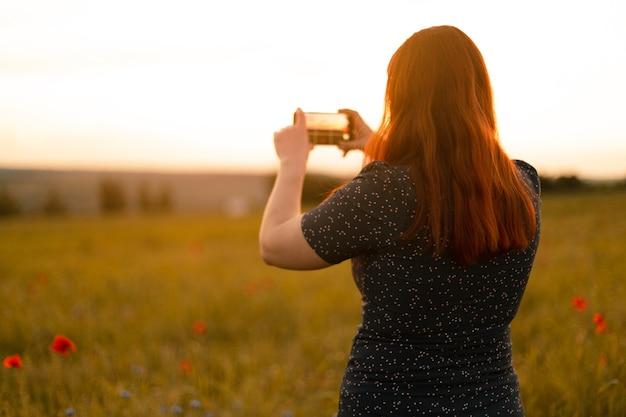 Achteraanzicht van een jong meisje in een zomerjurk maakt een foto op haar smartphone in een herfstveld op het gouden uur