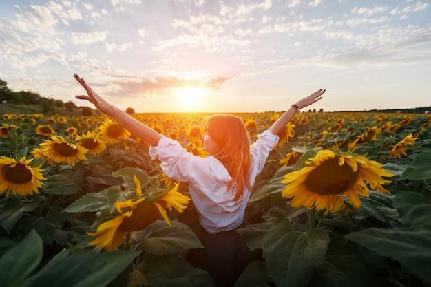 Achteraanzicht van een jong meisje in het midden van een landelijk gebied met zonnebloemen bij zonsondergang.