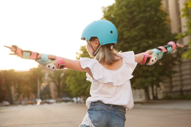 Achteraanzicht van een jong meisje met een helm en beschermende kleding op rolschaatsen buitenshuis