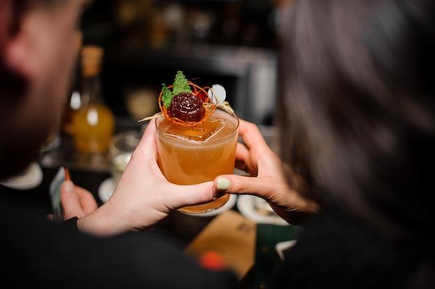 Achteraanzicht van een jong stel met een cocktailglas