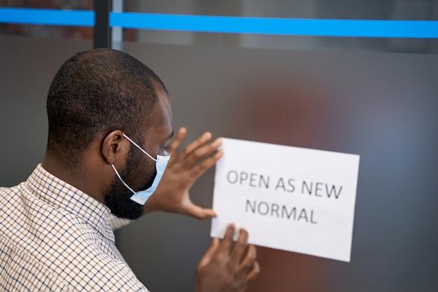 Achteraanzicht van een jonge afrikaanse man met een beschermend gezichtsmasker dat een open bord plakt met de tekst open as