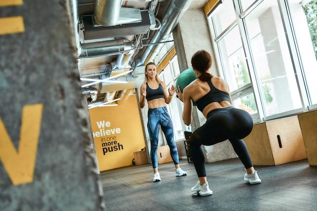 Achteraanzicht van een jonge atletische vrouw in sportkleding gehurkt met gewichtsbal op gym