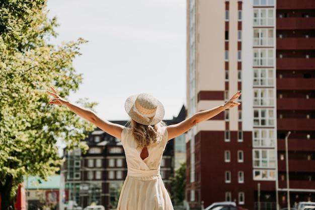 Achteraanzicht van een jonge gelukkige vrouw in een strohoed in een europese stad. trendy vrouwelijke reiziger op onbekende straat tijdens zomeravontuur