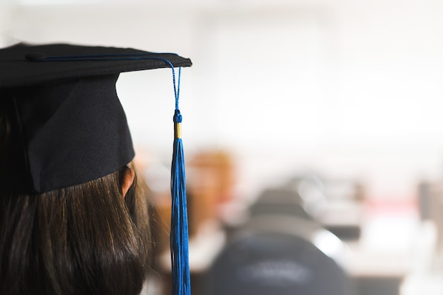 Achteraanzicht van een jonge, gelukkige zuidoost-aziatische vrouw die is afgestudeerd in afstudeerjurk en afstudeerpet op de universiteitscampus