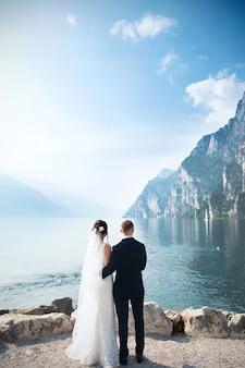 Achteraanzicht van een jonge geweldige bruidegom en bruid kijken naar het meer in de bergen tegen zonsopgang. bruiloft moment.