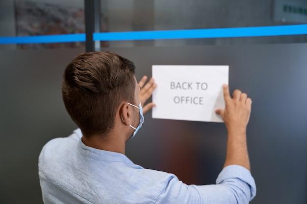 Achteraanzicht van een jonge kantoormedewerker met een beschermend gezichtsmasker dat een open bord met tekst plakt