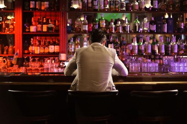 Achteraanzicht van een jonge man bier drinken