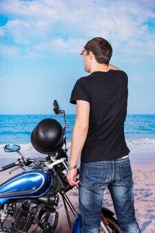 Achteraanzicht van een jonge man die in de verte kijkt en naast de klassieke blauwe motorfiets op het strand staat
