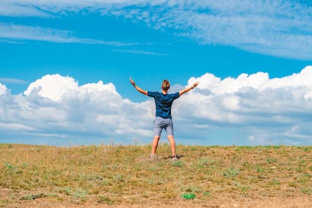Achteraanzicht van een jonge man die met zijn armen open staat tegen de achtergrond van een blauwe lucht