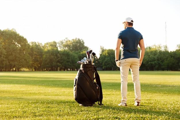 Achteraanzicht van een jonge man die op een groen veld