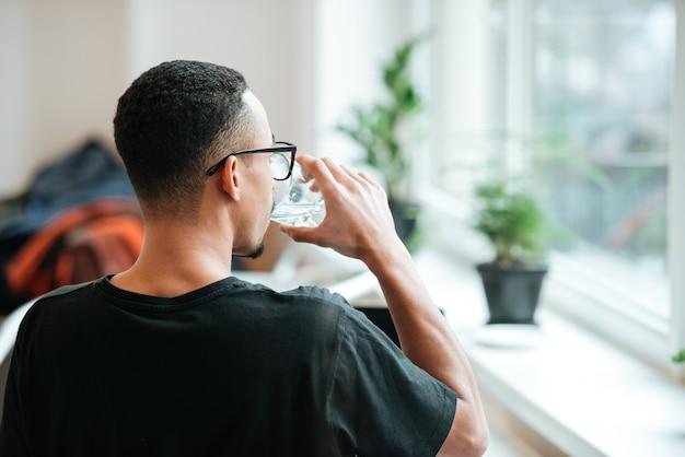Achteraanzicht van een jonge man die water drinkt uit glas tijdens de koffiepauze in café
