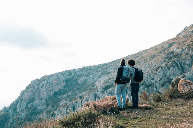 Achteraanzicht van een jonge mannelijke wandelaar met uitzicht op de berg