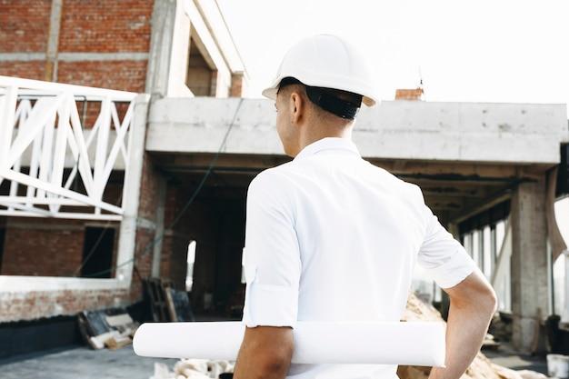 Achteraanzicht van een jonge meester die inspecteert hoe het werk aan het gebouw gaat en het plan van het gebouw vasthoudt.