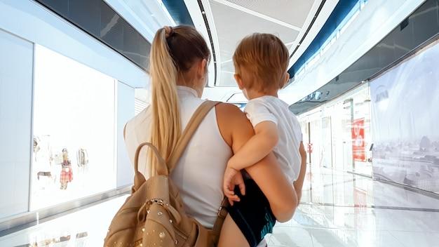 Achteraanzicht van een jonge moeder die haar zoontje vasthoudt en loopt in een groot modern winkelcentrum met veel winkels en winkels