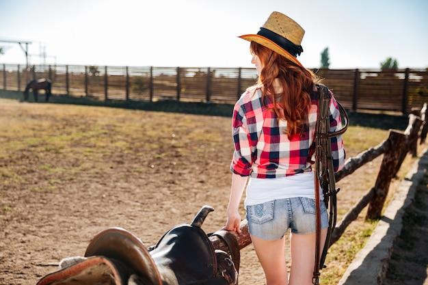 Achteraanzicht van een jonge veedrijfster in strooien hoed zadel voorbereiden op een rit