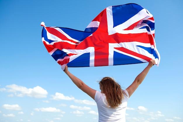 Achteraanzicht van een jonge vrouw die met de britse vlag zwaait