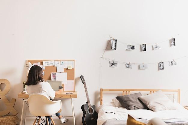 Achteraanzicht van een jonge vrouw die thuis werkt