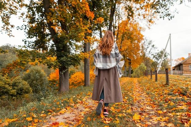 Achteraanzicht van een jonge vrouw in een stijlvolle jas in een modieuze sjaal in trendy sneakers in een herfstpark met bomen met oranjegeel blad. trendy meisje geniet van het herfstlandschap in het bos.