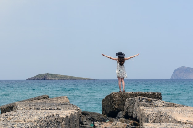 Achteraanzicht van een jonge vrouw in een witte zomerjurk en een hoed met zijn handen open is op de rotsen naar de zee. vrijheid, bevrijding, zonder grenzen, realiteit, leven