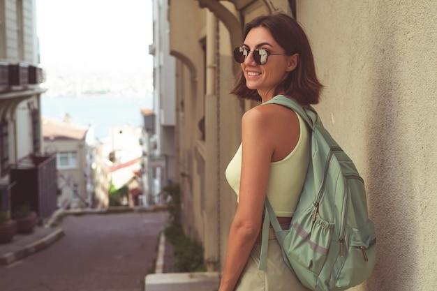 Achteraanzicht van een jonge vrouw in istanbul reist met een rugzak langs een turkse straat met uitzicht op de zee