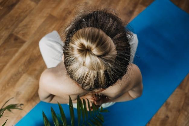 Achteraanzicht van een jonge vrouw in sportkleding die in lotuspositie zit terwijl ze thuis yogaoefeningen doet