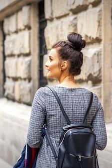 Achteraanzicht van een jonge vrouw met een rugzak loopt in een europese stad