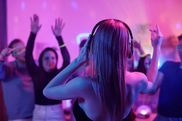 Achteraanzicht van een jonge vrouw met lang blond haar die een koptelefoon aanraakt terwijl ze voor een menigte opgewonden vrienden staat die dansen op een feestje