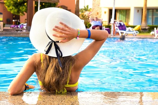 Achteraanzicht van een jonge vrouw met lang haar met een strohoed, ontspannend in de zomer in het hotelzwembad met blauw water op een zonnige dag.