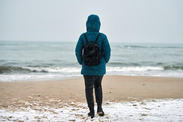 Achteraanzicht van een jonge vrouwelijke toerist in een groen donsjack en met een zwarte rugzak die op het zandstrand staat