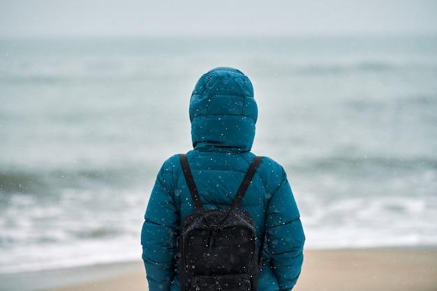 Achteraanzicht van een jonge vrouwelijke toerist in een groen donsjack en met een zwarte rugzak die op het zandstrand staat Premium Foto