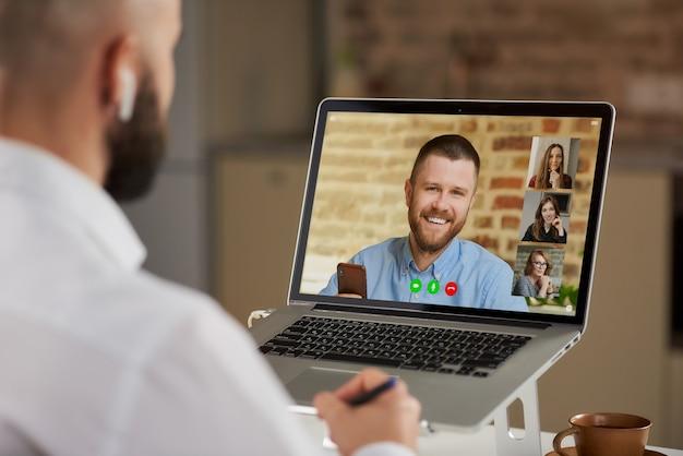 Achteraanzicht van een kale mannelijke werknemer in oortelefoons die notities doet tijdens een videoconferentie.