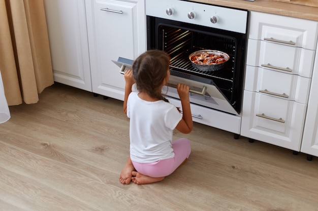 Achteraanzicht van een klein meisje dat wacht op het bakken van croissants, muffins of cupcakes in de buurt van de oven, kijkend in de oven zittend op de vloer, vrouwelijk kind met staartjes met een wit casual t-shirt.