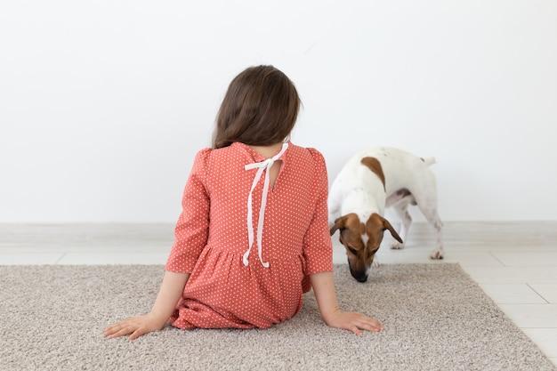 Achteraanzicht van een klein meisje in een rode polka dot jurk zittend op de vloer naast haar geliefde hond