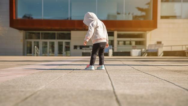 Achteraanzicht van een klein meisje met hoodie op zoek naar haar nieuwe sneakers op een stadsplein op een zonnige dag