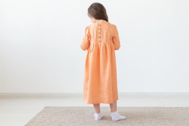 Achteraanzicht van een klein meisje poseren in een lange perzik jurk met knoppen op de rug en een wit oppervlak