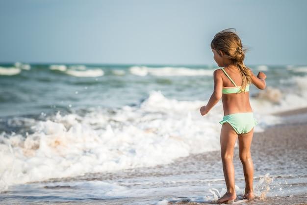 Achteraanzicht van een klein vierjarig meisje, zwemmen in de zee op een warme zomerdag tijdens zomervakantie in een tropisch land