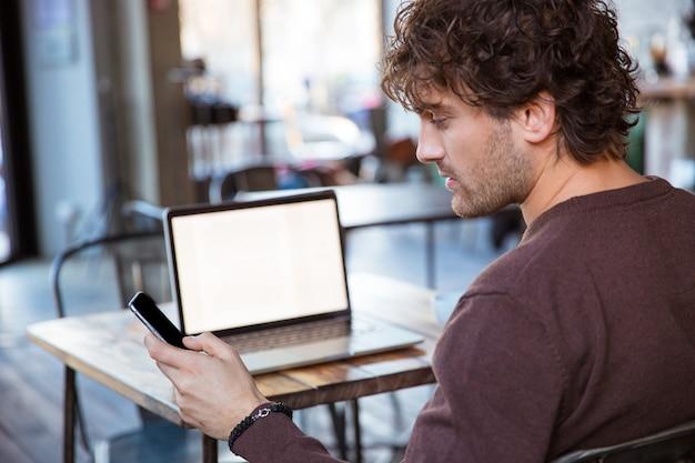 Achteraanzicht van een knappe, gekrulde, geconcentreerde aantrekkelijke man die een mobiele telefoon gebruikt terwijl hij met een laptop werkt