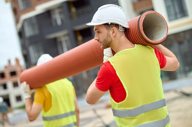 Achteraanzicht van een lader met een veiligheidshelm en een reflecterend vest aan het werk met zijn collega op de bouwplaats
